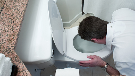 man throwing up in toilet bowl