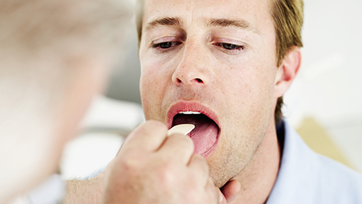 close-up of a human hand inserting a tongue depressor into a man's mouth